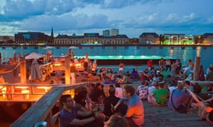 People drinking on the banks of the River Spree at sunset.