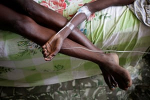 A boy rests his arm on his mother's legs as he receives treatment for cholera