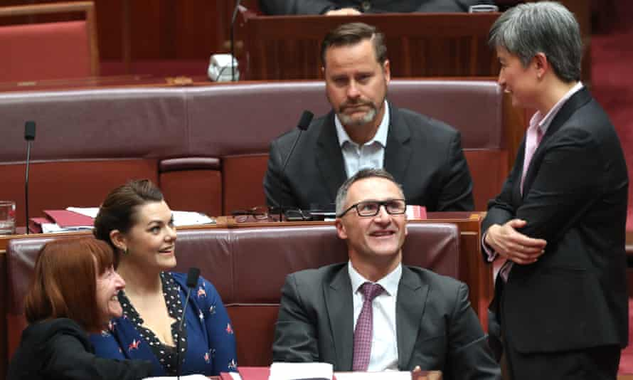Labor's leader in the Senate, Penny Wong, talks to Greens senators during the debate on the $144bn tax cuts package.