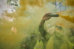 Paris, France. Gilets Jaunes (yellow vest) protesters chant against President Macron while waving symbolic yellow flares during a march