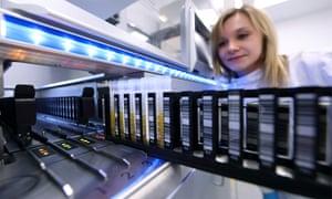 A researcher loads a batch of samples into a machine in a laboratory.