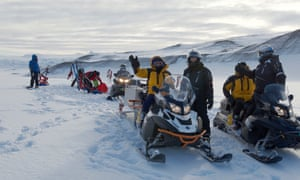 expedition members with sledges and other equipment  in a snowy landscape