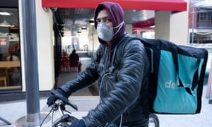 A Deliveroo rider wears a surgical face mask in Cardiff city centre