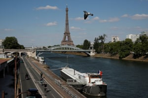 People ride bicycles on a bike path on the banks of the river Seine near the Eiffel tower in Paris
