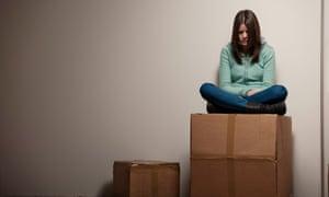 Teenage girl sitting on cardboard box.