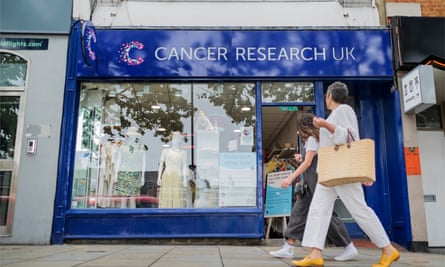 A woman walking past a Cancer Research charity shop.