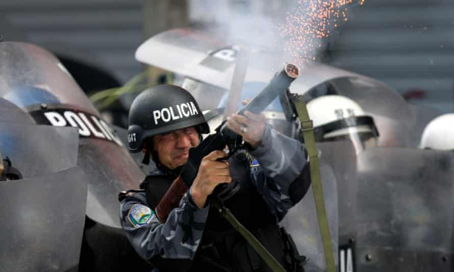 Honduran riot police shoot tear gas canisters towards supporters of ousted president Manuel Zelaya during protests in Tegucigalpa on 12 August 2009