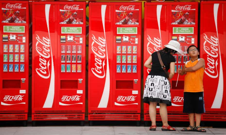 A  woman and boy next to Coca-Cola machines in Beijing