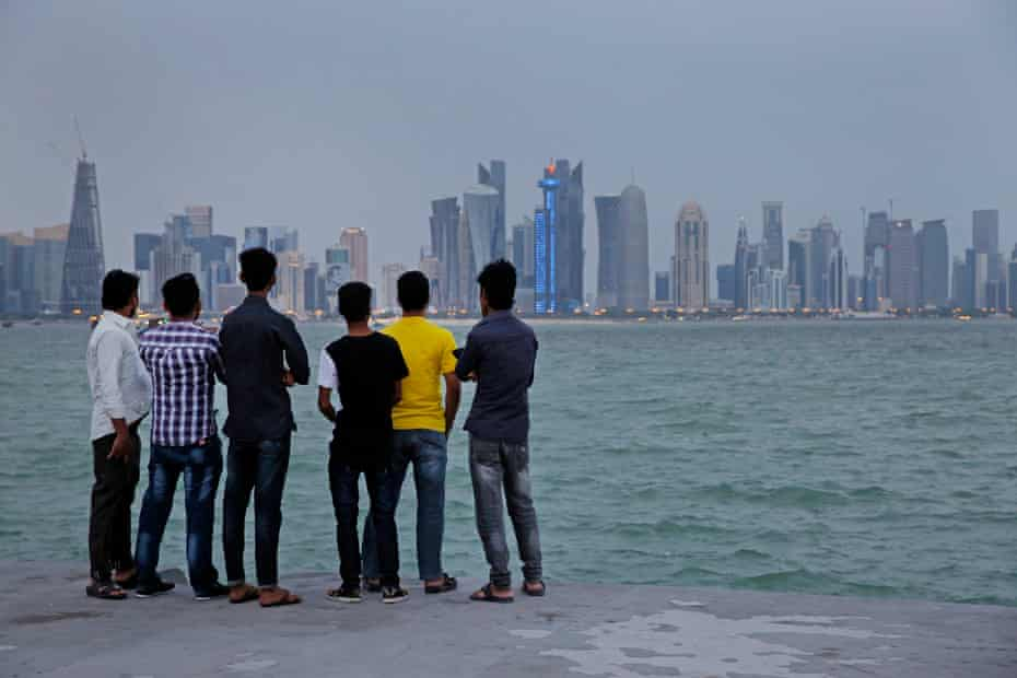 Migrant workers look across the water to the skyscrapers of West Bay in Doha on their day off.