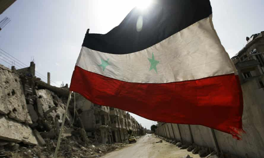 Reduced to rubble: a Syrian flag flutters outside a military barracks in the devastated Baba Amr neighbourhood.