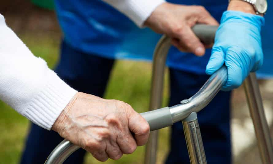 A carer helps a care home resident using a walking frame
