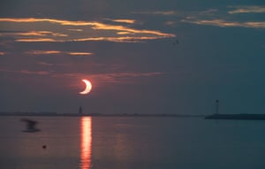 The partial eclipse as the sun rises behind the Delaware Breakwater lighthouse in Lewes. North-east states in the US saw a rare eclipsed sunrise, while in other parts of the northern hemisphere, the annular eclipse was seen as a visible thin outer ring of the sun's disk, not completely covered by the smaller dark disk of the moon: a so-called ring of fire