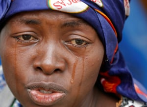 A woman cries after witnesses say her husband was killed when security forces burned down the headquarters of the main opposition party UDPS in Kinshasa