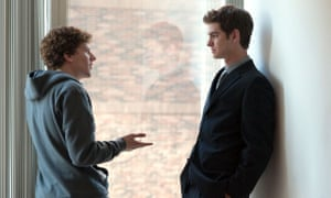 Jesse Eisenberg and Andrew Garfield standing facing each other, talking, in front of a window in The Social Network