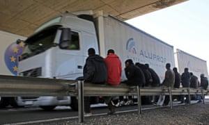 Migrants watch lorry
