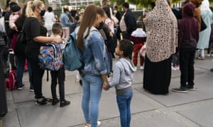 Children and relatives, wearing face masks, wait to enter the Heembeek primary school during the first day of term in Brussels, Belgium.