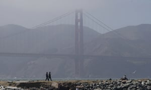 People walk on a path in front of the Golden Gate Bridge in San Francisco during the coronavirus outbreak.