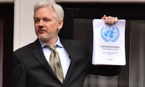 Julian Assange holds up copy of UN report into his detention