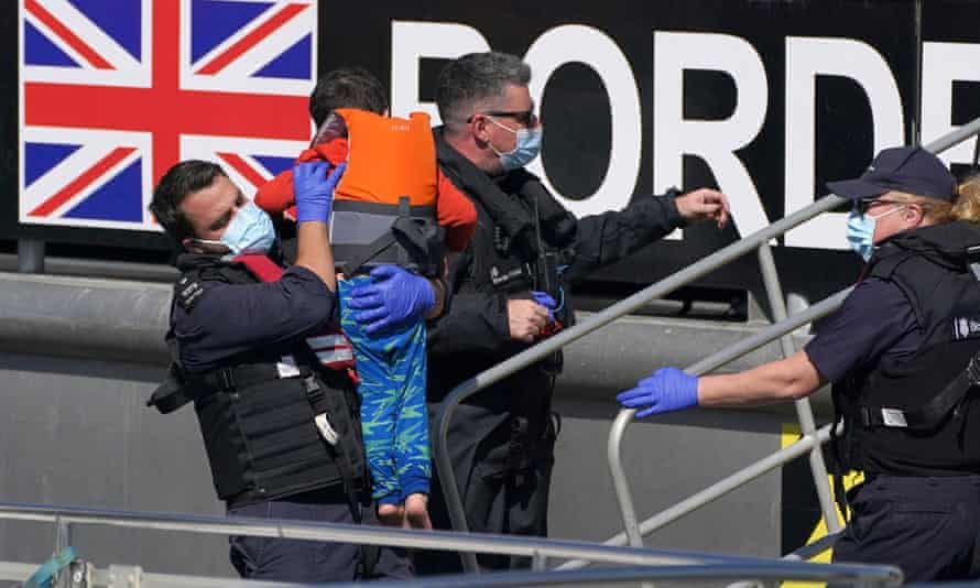 Border Force officers carry child in lifejacket