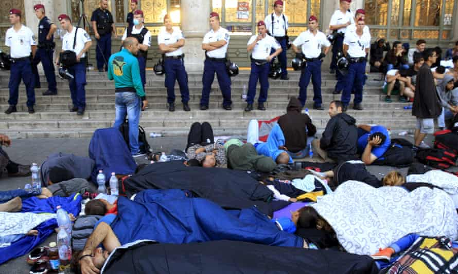 Hungarian police watch over migrants outside Keleti station in Budapest, Hungary.