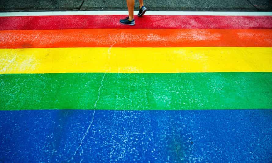 A pedestrian walks on a rainbow-colored crosswalk for Pride Week in Seattle in 2015.
