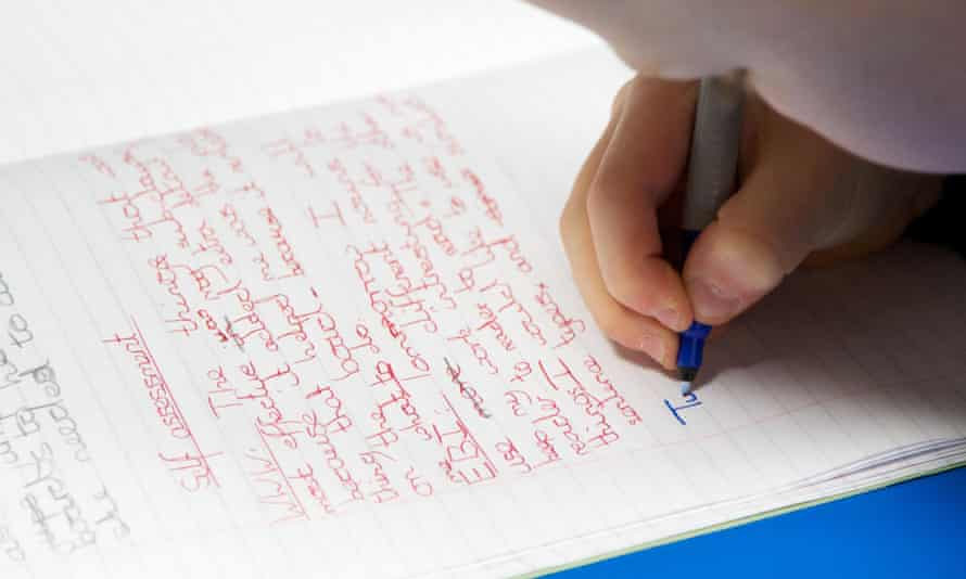 Primary school child writes in an exercise book