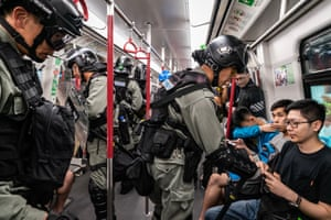 Riot police check passengers ID cards after charging onto a train at the Tung Chung MTR station. Protestors have blocked the transport routes to the Hong Kong International Airport on September 1, 2019.