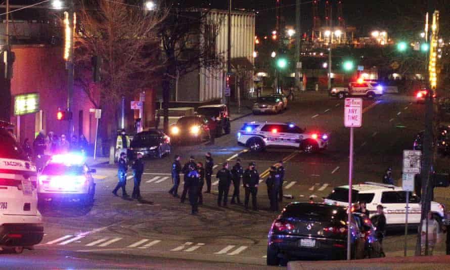 Tacoma police and other law enforcement officers stand in an intersection in downtown Tacoma, Washington.