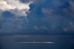 Storm clouds gather above the small huts and tower on Bikeman islet, located off South Tarawa in the central Pacific island nation of Kiribati