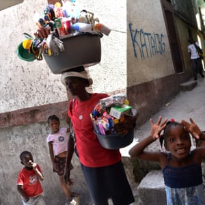 Port-au-Prince, Haiti On International Women's Day a woman sells cleaning products near children playing, in Jalousie neighbourhood, in the commune of Petion Ville