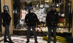Italian police officers stand in front of a shattered Gucci store window in Turin during a protest against coronavirus restrictions.