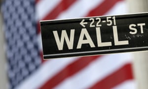 A Wall Street street sign is framed by an American flag