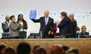 Laurent Fabius, COP 21 president and France's foreign minister, holds up the draft Paris outcome on 5 December 2015