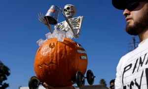 A man holds a Jack O'Lantern topped with a skeleton doing the ALS ice bucket challenge during Halloween pumpkin races in Manhattan Beach, California