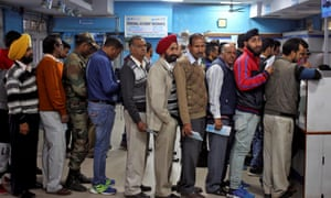 People queue as they wait to exchange or deposit their old high denomination banknotes in Jammu, India.