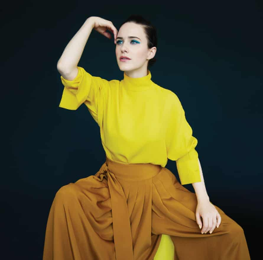 Rachel Brosnahan in a bright yellow lose-fitting top with a polo neck and orange/gold billowing trousers