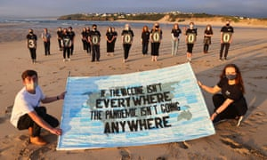 Activists from Crack the Crisis hold an installation during a vigil for the people around the world who have passed away due to the coronavirus disease (COVID-19) on the sidelines of G7 summit, at Porthkidney beach near Carbis Bay, Cornwall, Britain.
