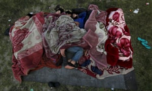 People sleep on the ground in an open area