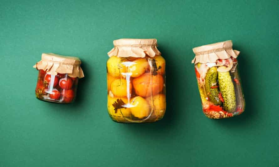cucumber, squash and tomatoes pickling in glass jars
