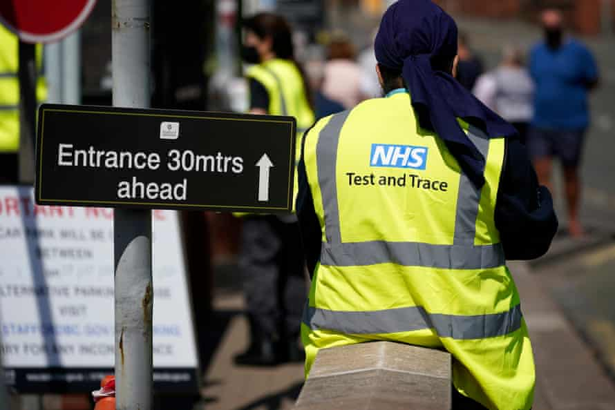 A Serco employee working on behalf of NHS Test and Trace seen from behind wearing an NHS hi-vis jacket