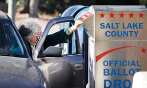 A voter drops off her mail in ballot at a drop box at the Salt Lake County election office in Utah.