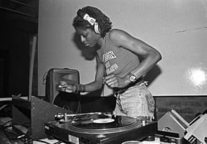 """DJ Paulette, Paradise Factory, 2001 – Al Baker """"Paulette is an internationally renowned DJ who cut her teeth on Manchester's queer scene, holding residencies at the Number One Club and Flesh at the Haçienda in the early 90s. She's pictured here at Paradise Factory – a three- storey queer club in the former offices of Factory Records."""""""