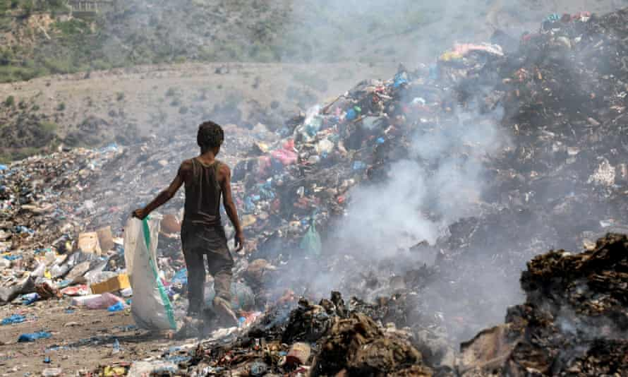 A young boy picks material from a rubbish dump in Taez, Yemen.