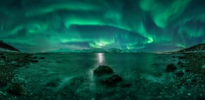 <strong>Aurora Panorama 3 </strong> The vivid green Northern Lights dance above Lyngenfjord, Norway, tracing out the shape of the Earth's magnetic field above the waters. Green, the most common colour associated with aurorae, is produced by oxygen atoms and molecules energised by the impact of solar particles that have escaped the sun's atmosphere, causing them to glow brightly