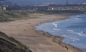 People walk along the beach in Saltburn By The Sea