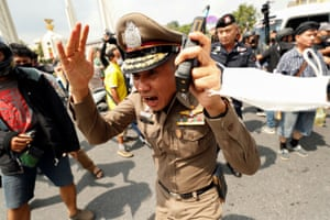 Bangkok, Thailand. A police officer reacts during clashes between pro-democracy demonstrators and royalists during an anti-government protest, on the 47th anniversary of the 1973 student uprising