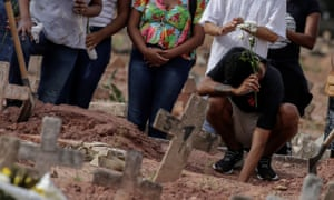 People stand around a grave in a cemetery