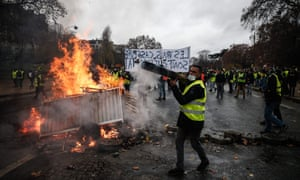 Yellow vests build a barricade during a protest against rising oil prices and living costs.