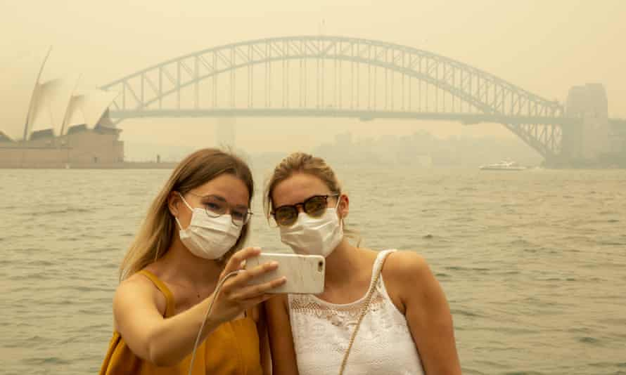 German tourists Julia Wasmiller, left, and Jessica Pryor take a selfie wearing face masks due to heavy smoke in Sydney, 19 December 2019