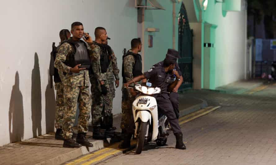 Maldivian security officers stand guard near the president's official residence in Malé